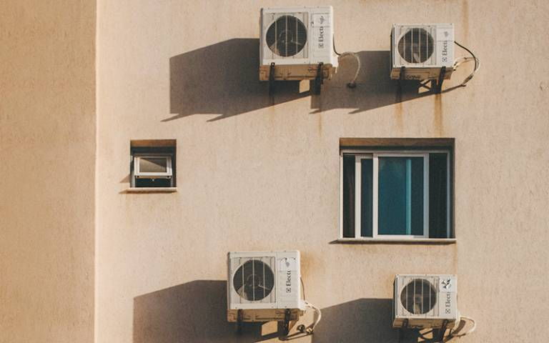 Air conditioning units on the side of an apartment block