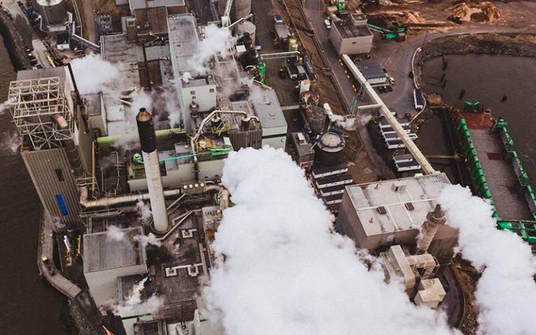 Photo shows an aerial view of a power station with thick grey smoke billowing from chimneys.