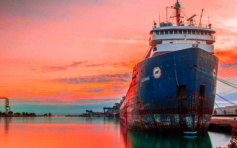 Photo of a cargo ship against a sunset background