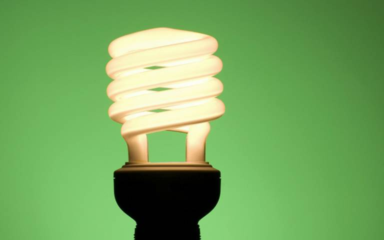 Image shows an energy saving light bulb against a green background.