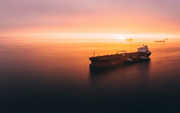 Photo shows freight ship in the sea against a sunset background.
