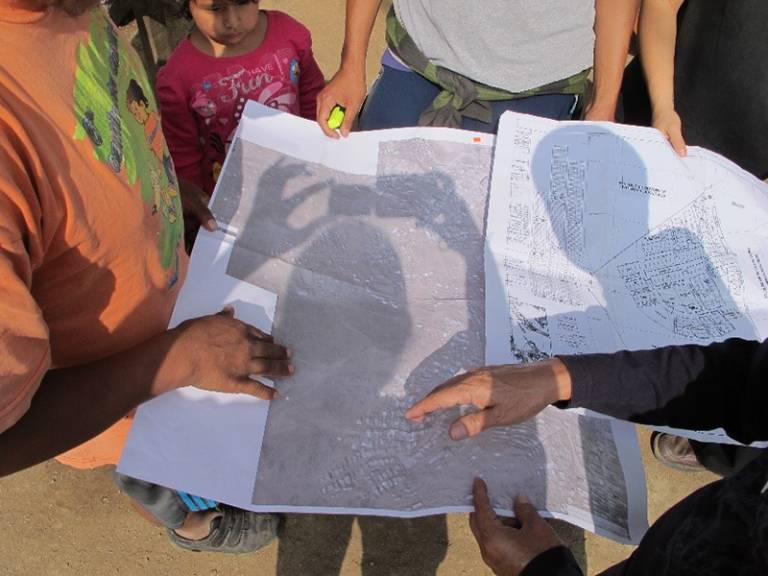 Photo shows locals in Lima, Peru, holding an aerial map of the area