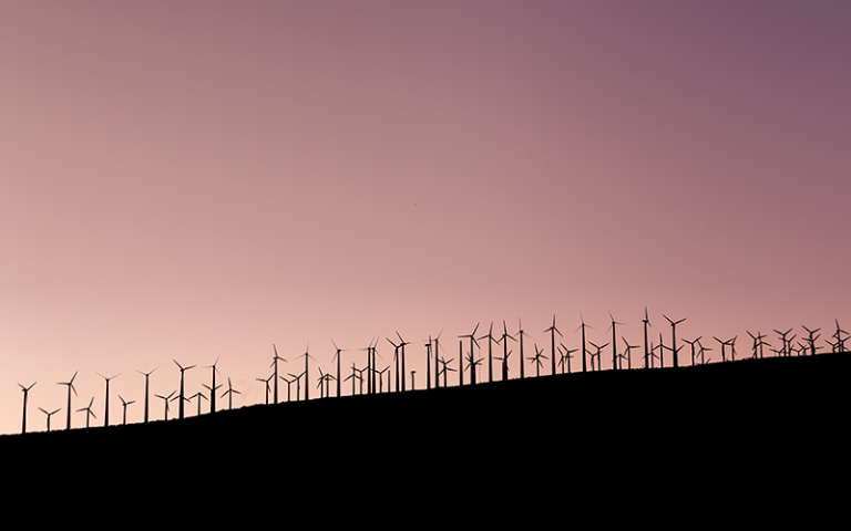 Photo shows silhouette of wind turbines against a pink sunset