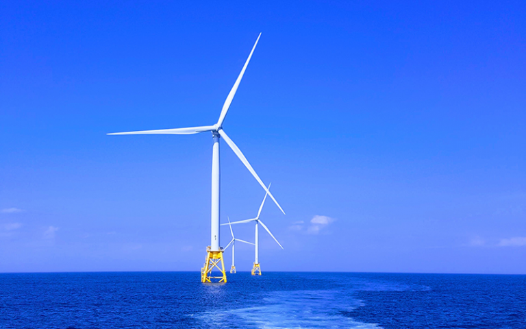 Photo shows a row of wind turbines stationed at sea with a blue sky behind