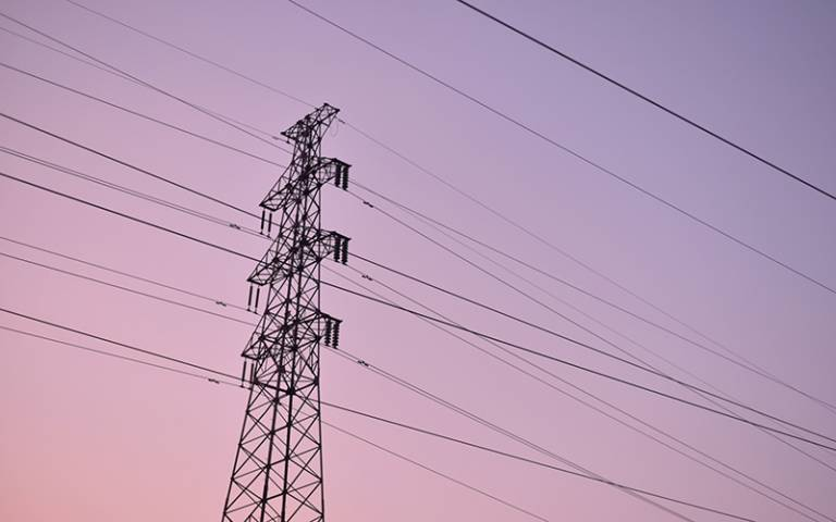 Photo of a pylon and cables against a pink sunset.