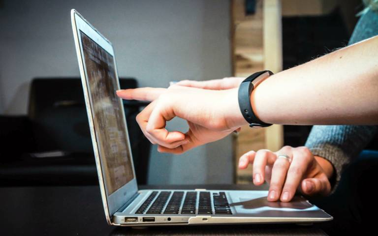 People pointing at a laptop