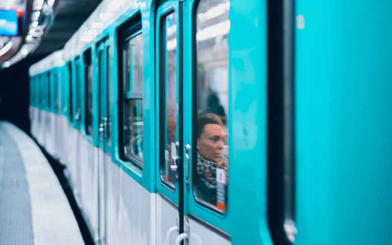 Photo shows a blue metro train, passengers can be seen sitting in the carriage through the window.