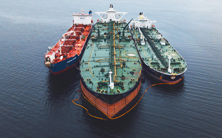 Photo shows three oncoming green and red freight ships.