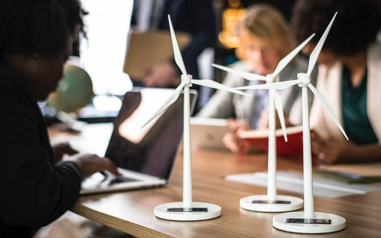 Wind turbine models of a desk next to people working