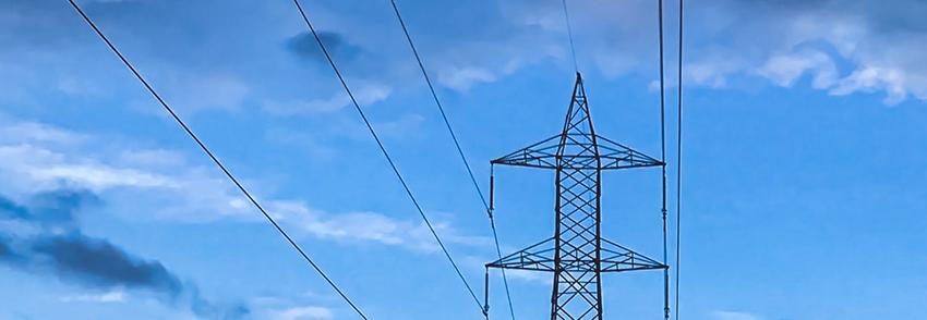 An electricity pylon on the backdrop of a blue sky