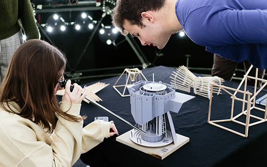 Student testing light levels on an architectural model in The Bartlett's artificial sky