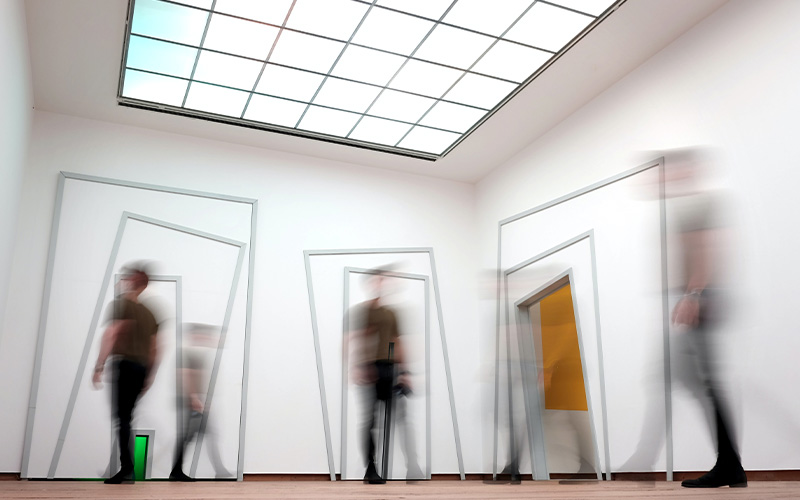 room full of blurred people with large skylight