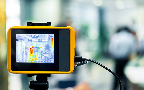 Someone using a thermal imagining camera in an office environment