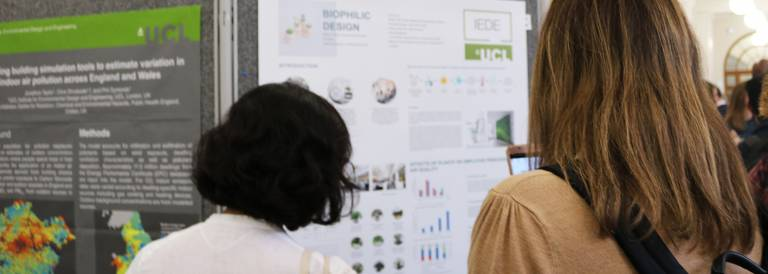 People looking at a display of PhD research posters