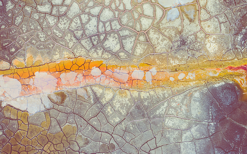 Abstract photo of a yellow and gray concrete surface from above, that looks like an aerial landscape photo.