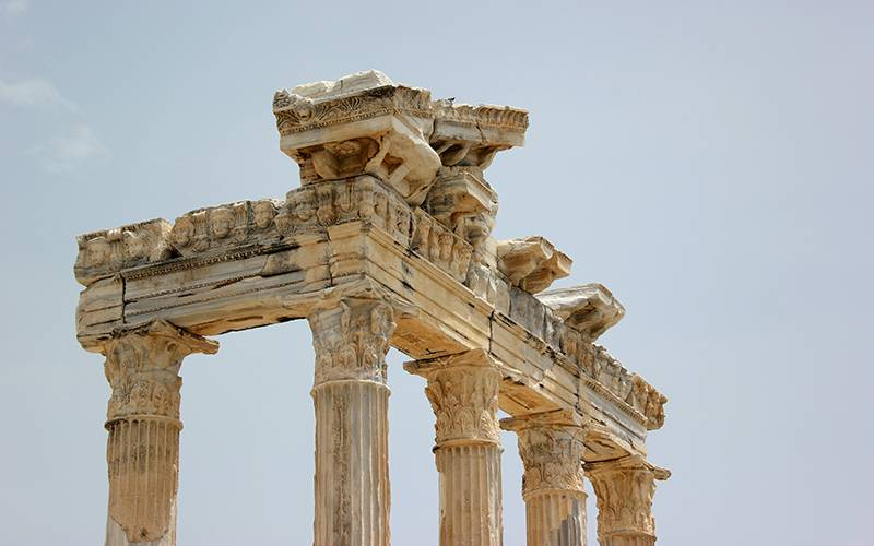 Photo shows the columns and pediment of an ancient classical temple ruin against a blue sky.