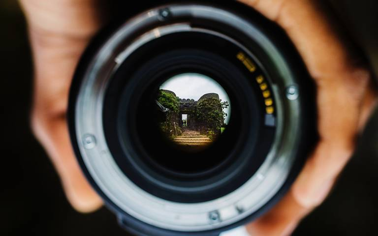 Photo shows hands holding a camera lens, the lens reflects a view of a castle