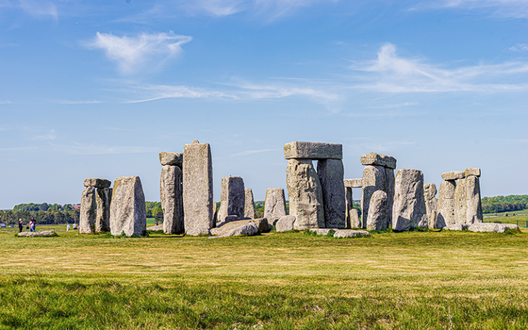 Photo shows Stonehenge site, a gray rock formation on a green grass field during daytime