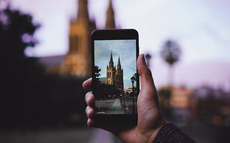 Photo shows a phone taking a photograph of a church and street