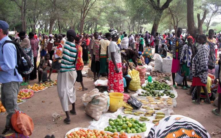 A group of people buying and selling fruit and vegetables at an outdoor market in Africa