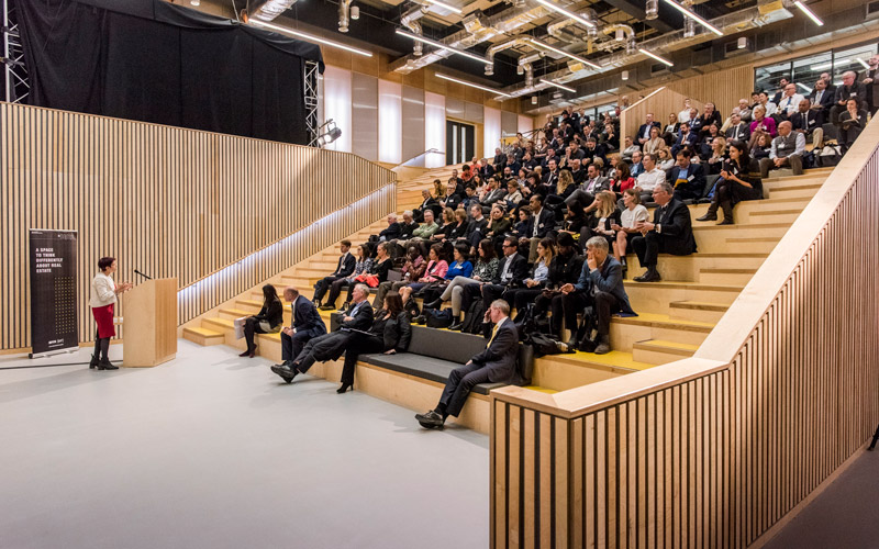A lecturer delivers a talk in front of a large group of people in a lecture theatre