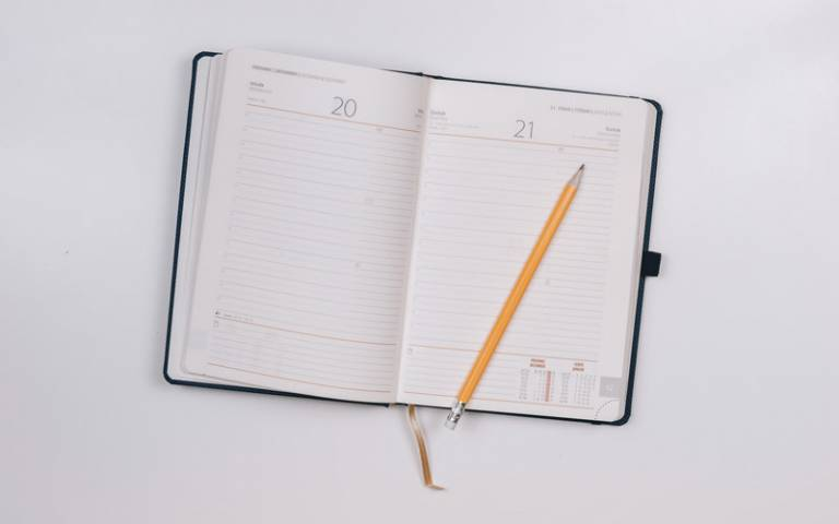 A diary opened with a pencil on top