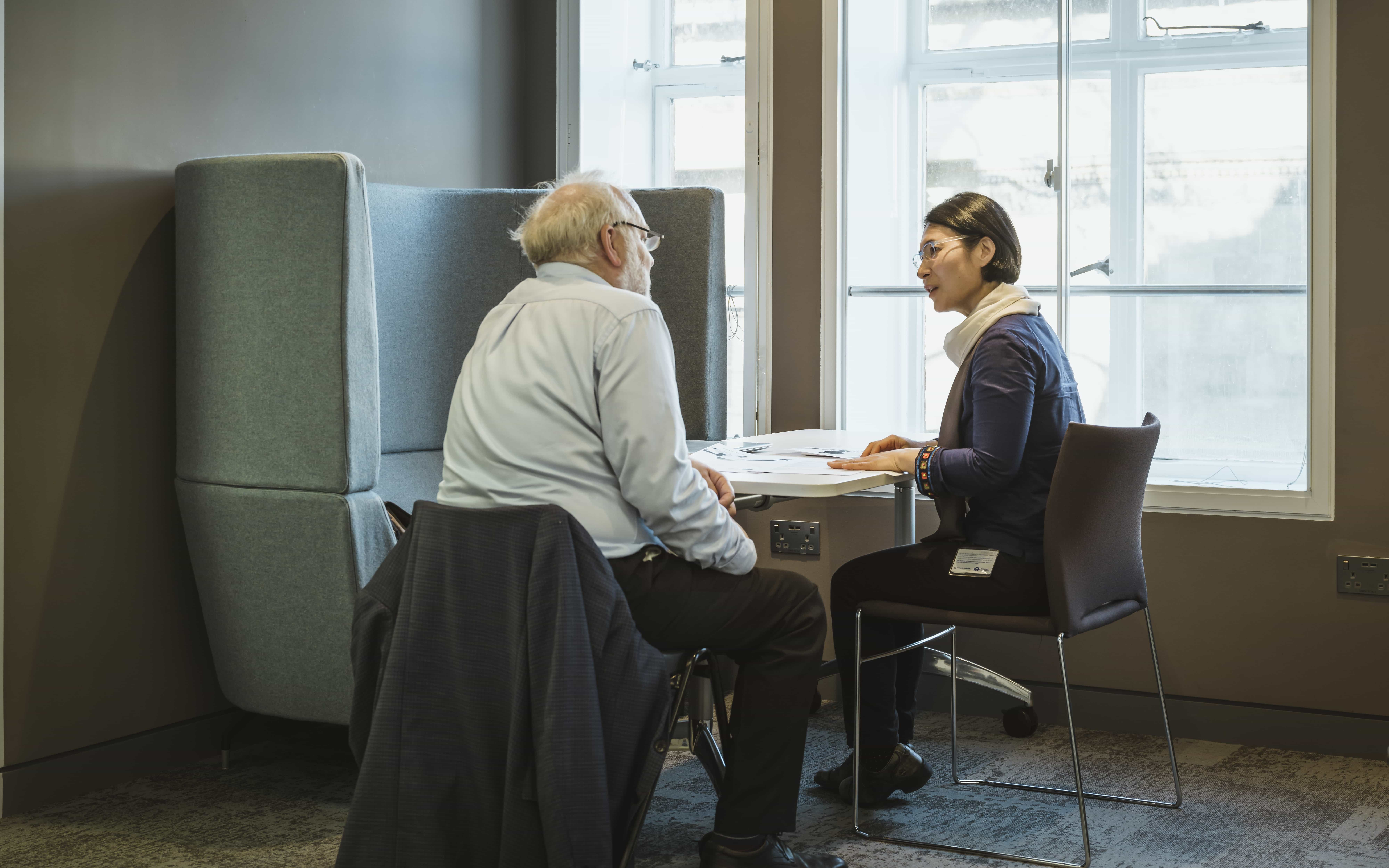 An academic talks to a mature student, they are sitting at a desk with documents in front of them
