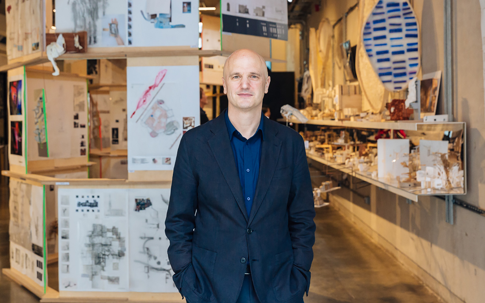 An image of Christoph Lindner standing in front of student work at 22 Gordon Street, London, home of The Bartlett School of Architecture