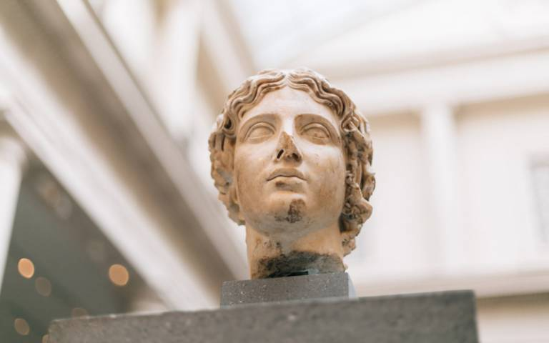 The head of an ancient statue, on display in a museum setting