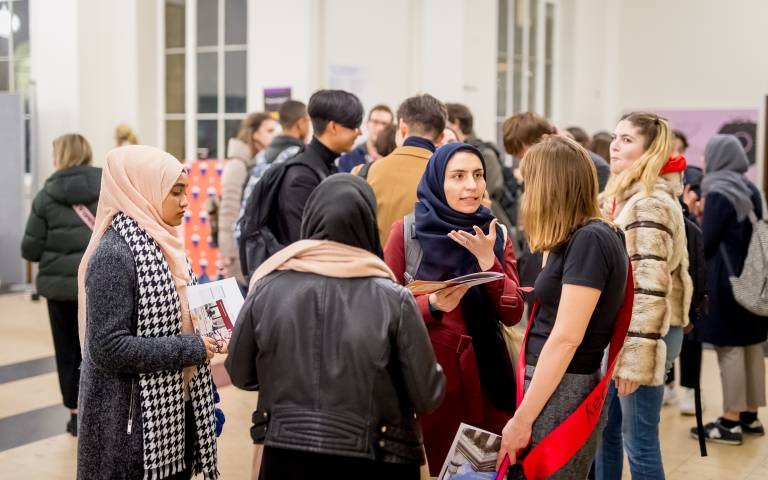 a woman talks to an open day volunteer at the UCL open event