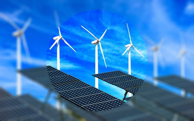 Wind turbines and solar panels against blue sky with blur