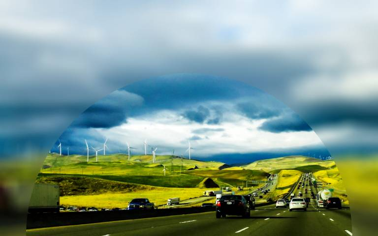 Cars in traffic with wind turbines on the horizon