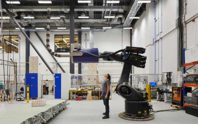 A Bartlett student stands underneath a huge robotic arm