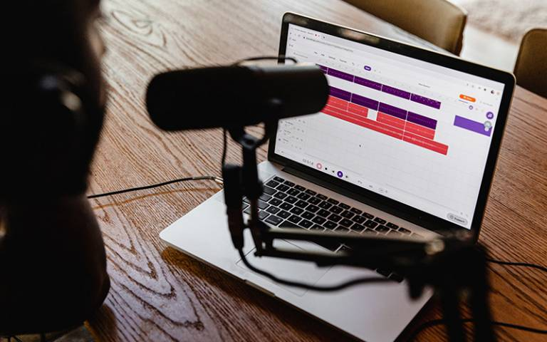 Image of laptop and podcast microphone on wooden table