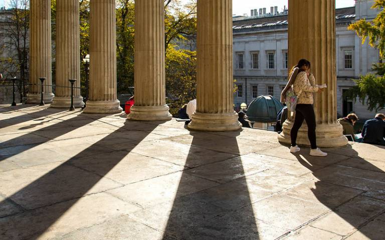 Student walks across the portico at the UCL Wilkins Building