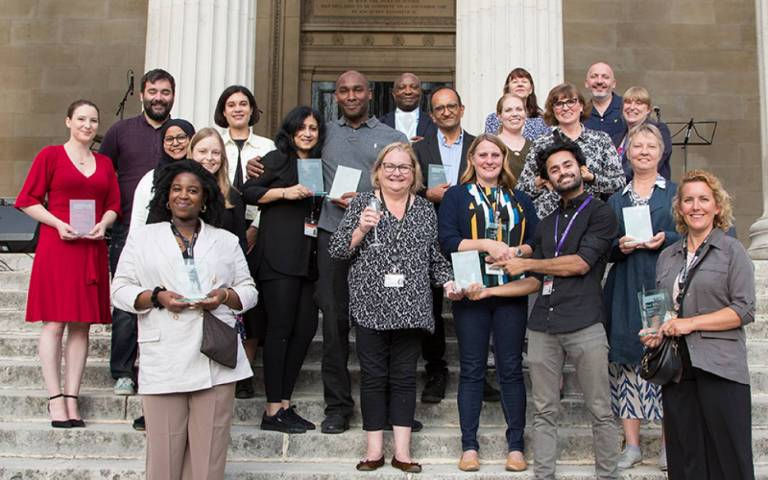 Group of UCL staff standing on stairs at main UCL campus, holding glass awards