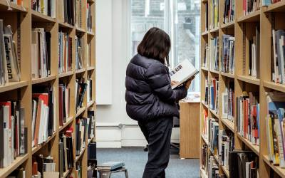 A person studies a book while standing between two shelves of library books