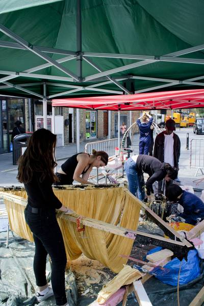 Group of five students outside under tent, constructing wooden triangular frame with clamps and yellow fabric draped inside frame.