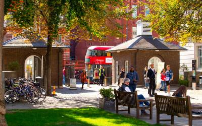 A red London bus drives past a sunny autumnal park in London
