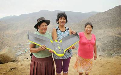 Three ladies holding a drone in a mountain landscape
