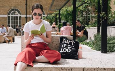 A student sits on campus reading a book with a Bartlett 100 campaign tote bag and reusable water bottle next to them