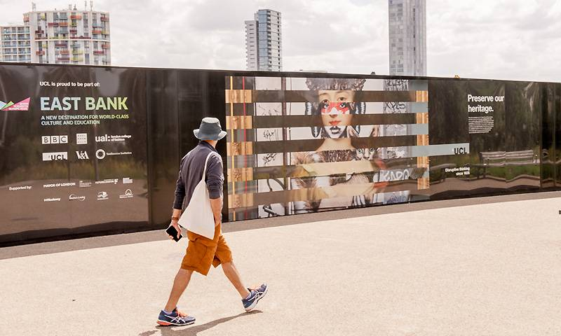 A person walks past colourful hoardings in East London