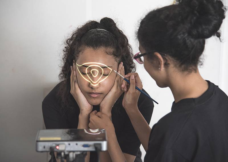 Image of two students. One student has their head in their hands and a triangular shape projected onto their face. The second student is holding a small paint brush in their right hand, close to student one's face.