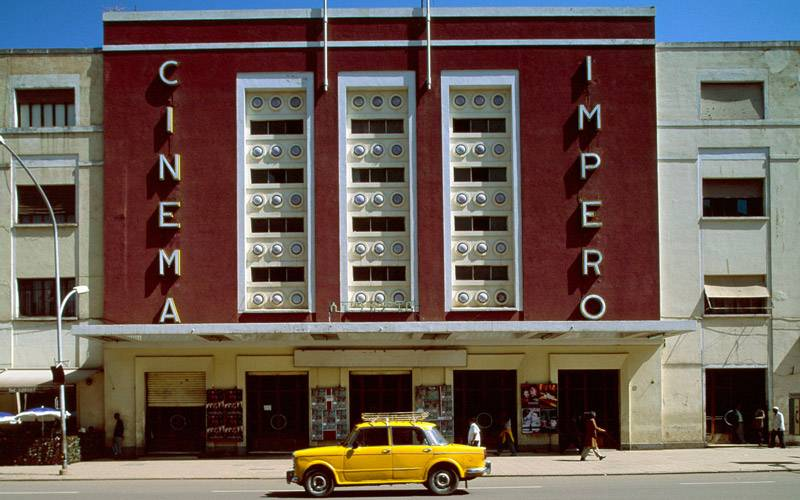 A photograph of cinema Impero, built in 1937, designed by Mario Messina. There is a vintage yellow car parked in front of the building. Image by Edward Denison.