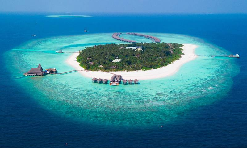 An aerial view of a largely undeveloped 'paradise' island, with white sand and surrounded by clear blue water