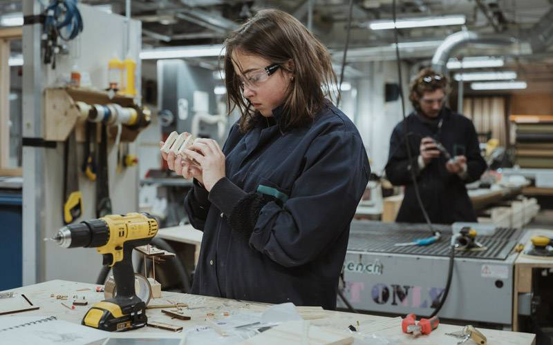 A female student creating a model in the Bartlett workshop, with drills and machinery around her, and a male student working in the background