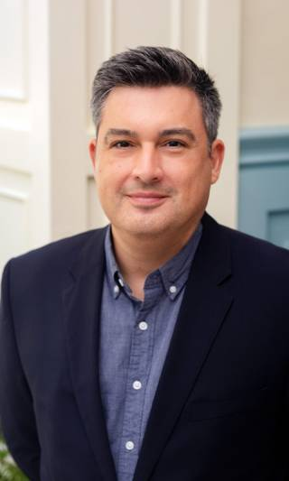 A profile image of Dr Brian Garcia who is wearing a blue shirt and navy jacket