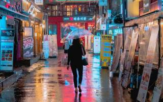 An image of a person walking down a brightly lit street in South Korea, lots of neon lights