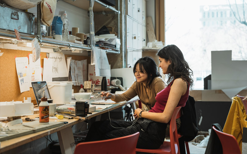 Two students at their workspaces in 22 Gordon Street architecture school