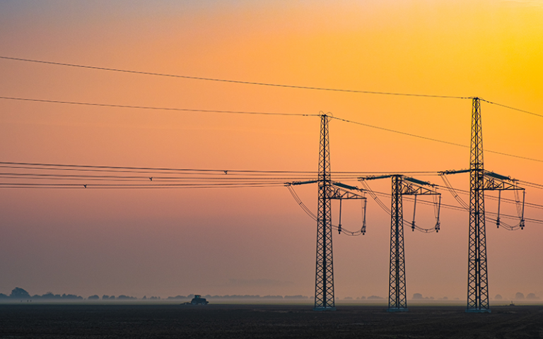 Photo shows three electricity transmission towers with a sunset in the background.